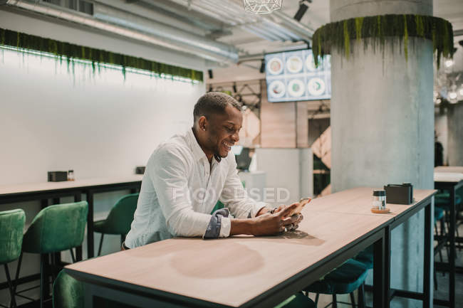 Side view of handsome African American man smiling and using modern smartphone while sitting at table in stylish cafe — Stock Photo