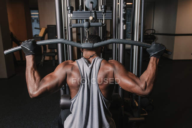 Black man exercising on machine in gym — Stock Photo