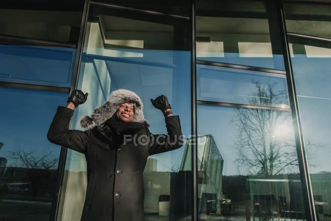 Рукопожатный афроамериканец в теплой одежде улыбается и жестикулирует руками, празднуя успех у стеклянной стены современного здания — стоковое фото