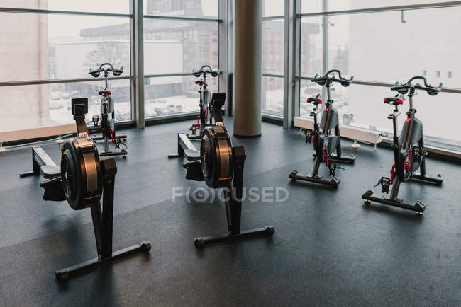 Exercise machines near huge window in gym — Stock Photo