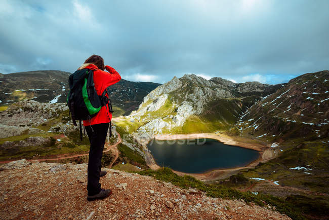 Back view of woman with backpack taking picture of amazing small lake with clean water on cloudy weather in beautiful mountainous countryside — Stock Photo