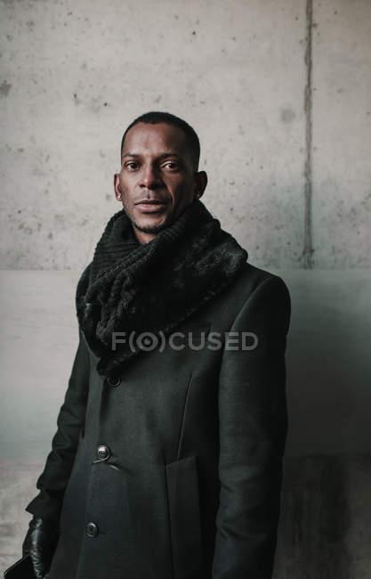 Bonito homem afro-americano em roupas quentes elegantes que estão perto da parede de concreto — Fotografia de Stock