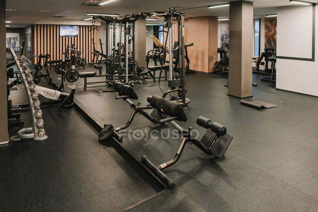 Various exercise machines standing inside spacious stylish room of modern gym — Stock Photo