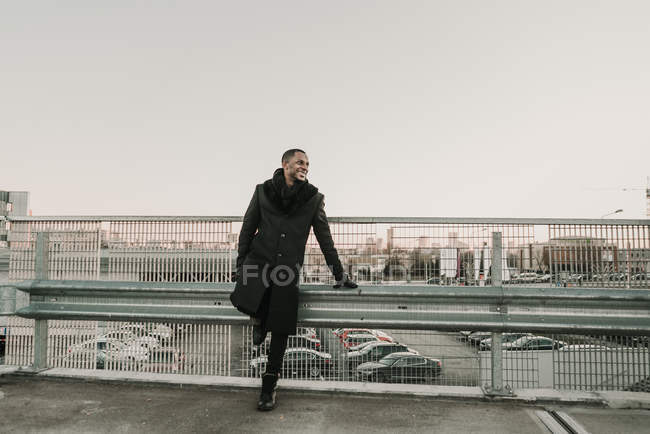Handsome African American man in elegant coat smiling and looking away while leaning on overpass railing on background of parking lot and modern city — Stock Photo