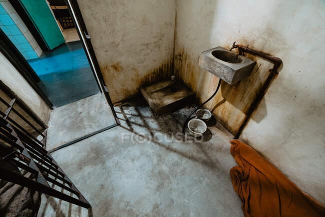 Pequena pia grungy anexada à parede de concreto perto da porta aberta de sujo na prisão em Oviedo, Espanha — Fotografia de Stock