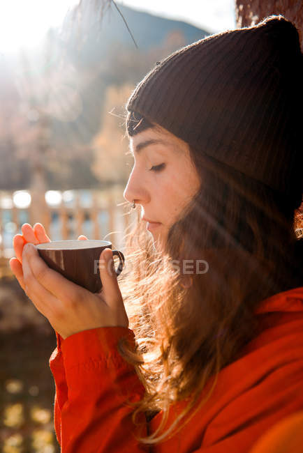 Side view of beautiful young female in stylish hat keeping eyes closed and smelling aromatic hot drink while sitting in countryside on sunny weather — Stock Photo