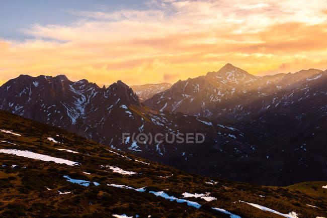 Чудовий хмарний небо над сніжною гірським діапазоном в прекрасному вечорі в природі — стокове фото