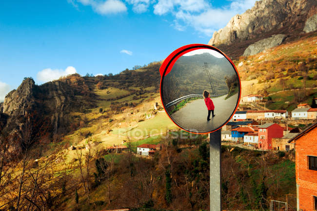 Round street mirror with reflection of unrecognizable female standing against small settlement and majestic mountains — Stock Photo