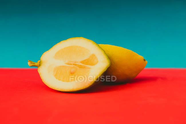 Duas metades de limão maduro suculento na superfície vermelha vívida em fundo azul — Fotografia de Stock