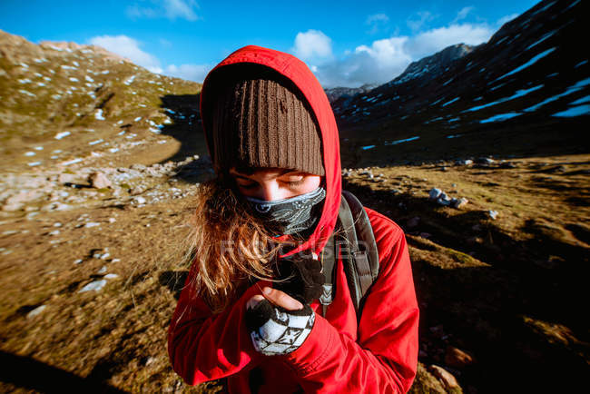 Young woman in warm clothes standing amidst snowy mountains on sunny weather in wonderful countryside — стокове фото
