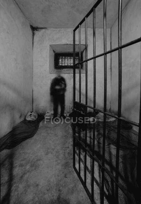 Невпізнаваний розмитий чоловік стоїть біля брунатного бетонного муру в тюремній камері в Ов