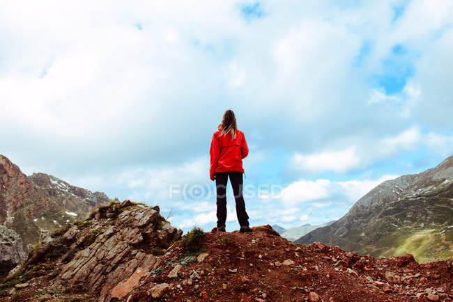 Back view of woman in red jacket standing on stony ground and looking at mountainous countryside against cloudy sky — Stock Photo