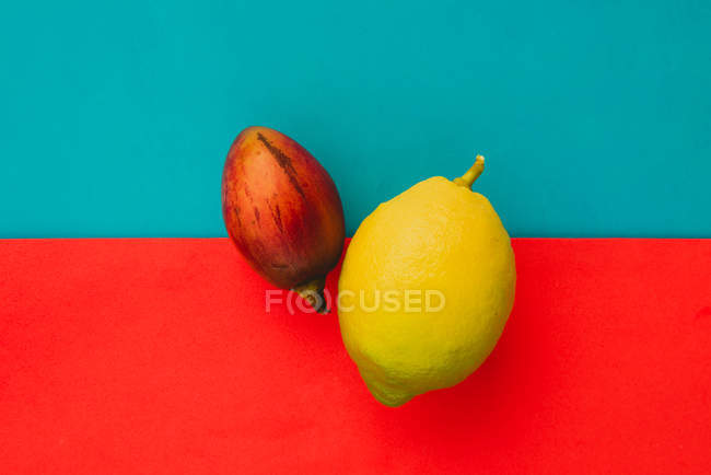 Fresh whole tamarillo and ripe lemon on bright red and blue background — Stock Photo