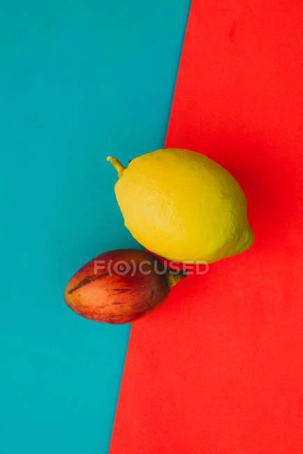 Свіжі весь tamarillo і стиглі лимона на фоні яскравий червоний і синій — стокове фото