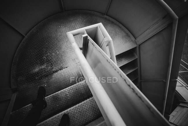 Ноги анонимного человека, стоящего на металлической спиральной лестнице внутри тюрьмы в Овьедо, Испания — стоковое фото
