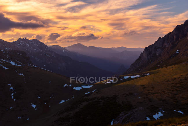 Magnificent cloudy sky over snowy mountain range in beautiful evening in nature — Stock Photo