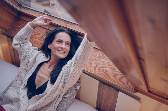 Веселая женщина указывает на оконное стекло — стоковое фото