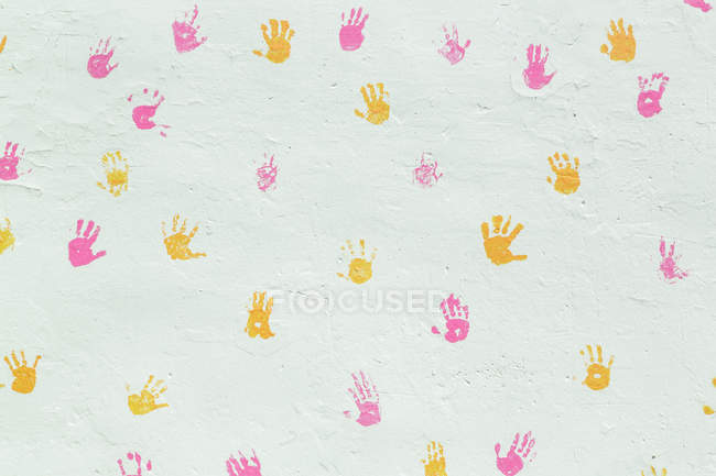 Pink and yellow hand prints decorating surface of white stucco wall — Stock Photo