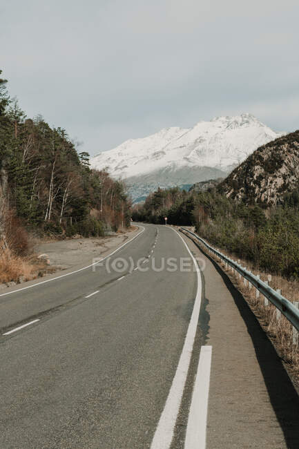 Countryside route on valley with woods and wonderful snowy mountains in Pyrenees — Stock Photo