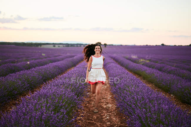 Happy attractive lady in dress running between rows of beautiful purple flowers on lavender field — Stock Photo
