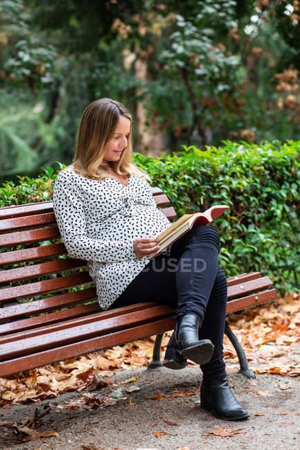 Donna attraente incinta con libro seduto sulla panchina — Foto stock