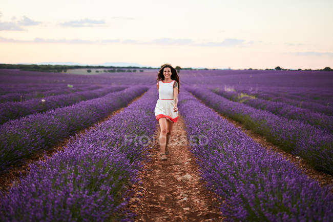 Young woman running between rows of violet lavender field — Stock Photo
