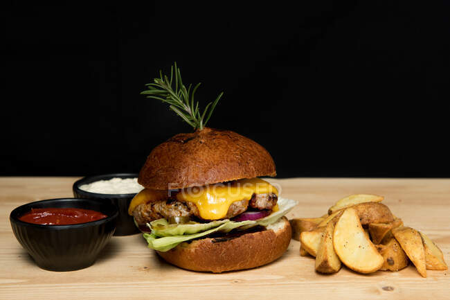Розташування чаш з соусами на дерев'яному столі біля смачного бургера і шматочків смаженої картоплі. — стокове фото