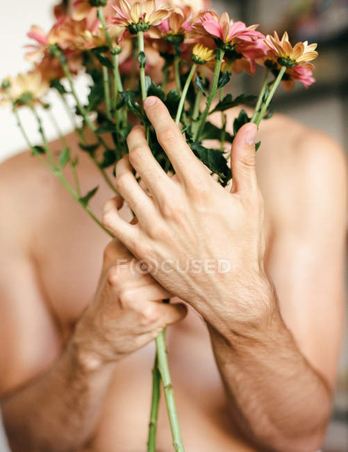 Young shirtless guy holding flowers on grey background — Stock Photo