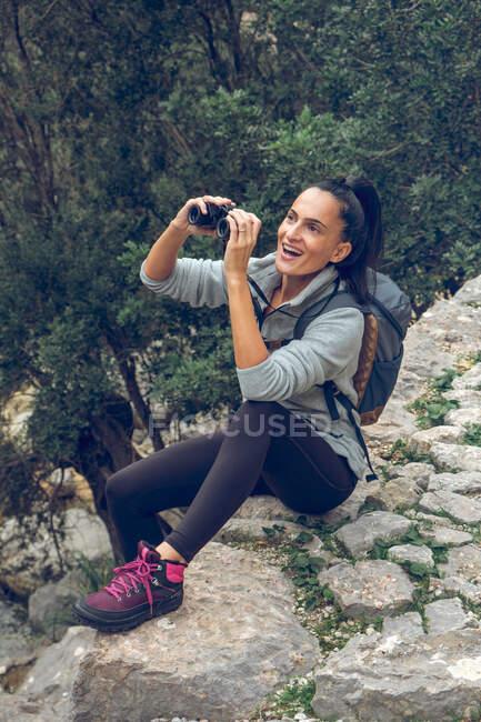 Bella donna sorridente e guardando la distanza attraverso il binocolo moderno mentre sedeva sul sentiero di pietra sul ruscello calmo nel parco Soller, Spagna — Foto stock