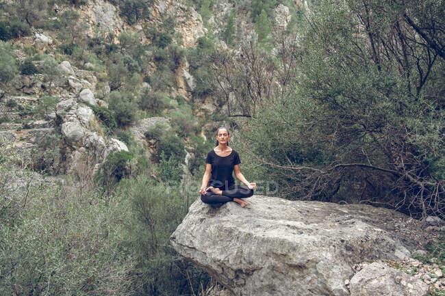 Belle femme en tenue de sport gardant les yeux fermés et méditant tout en étant assis dans la pose de lotus sur la pierre brute dans un beau parc — Photo de stock