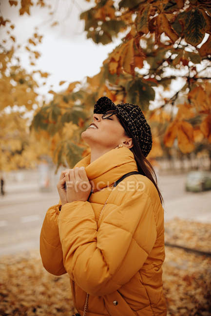 Smiling young woman in stylish warm clothes standing in autumn park — Stock Photo