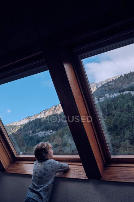 Niño mirando a la montaña a través de la ventana - foto de stock