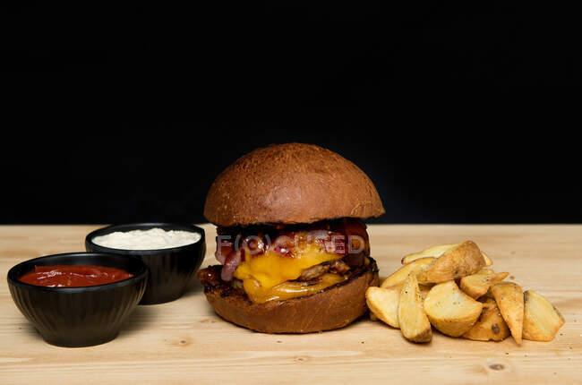 Cuencas de cierre con salsas en la mesa de madera cerca de un delicioso hamburguesero y trozos de patata asada. - foto de stock