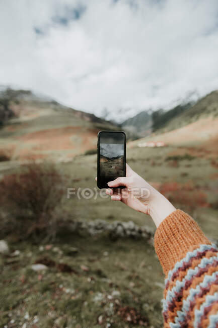 Crop hand of lady with mobile phone shooting picturesque view of valley with wonderful mountains and cloudy heaven in Pyrenees — Fotografia de Stock