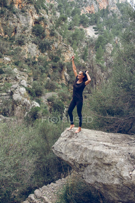 Attractive female in casual outfit smiling with arms up on edge of rough stone near wonderful mountain in beautiful park — Stock Photo