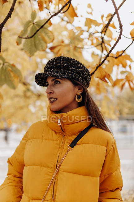 Young woman in stylish warm clothes standing in autumn park — Stock Photo