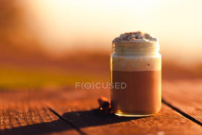 Aromatic cinnamon sticks near jar of yummy coffee with cream on lumber tabletop — Stock Photo