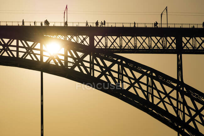 Силуэт моста с людьми, идущими против яркого золотистого солнечного света вечером — стоковое фото