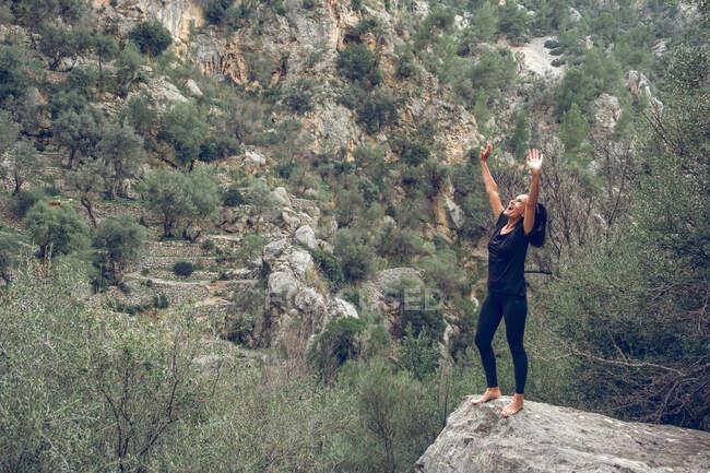 Attraente femmina in abito casual sorridente e cercando di mantenere l'equilibrio sul bordo della pietra rouf Ligugh vicino meravigliosa montagna in un bellissimo parco — Foto stock