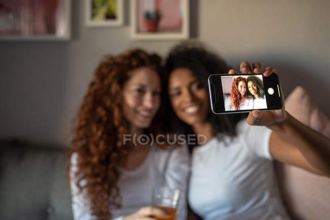 Jovens mulheres alegres amigas sentadas relaxadas no sofá com telefone celular tirando uma selfie — Fotografia de Stock