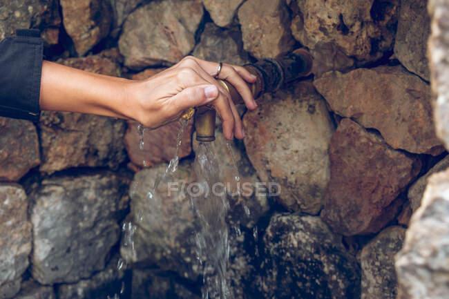 Hand eines anonymen Weibchens liegt auf Wasserhahn mit sauberem Süßwasser in der Nähe der gealterten Steinmauer — Stockfoto