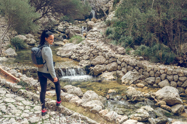 Back view of female with backpack standing on a stone path near a river with fresh clean water in amazing park — Stock Photo
