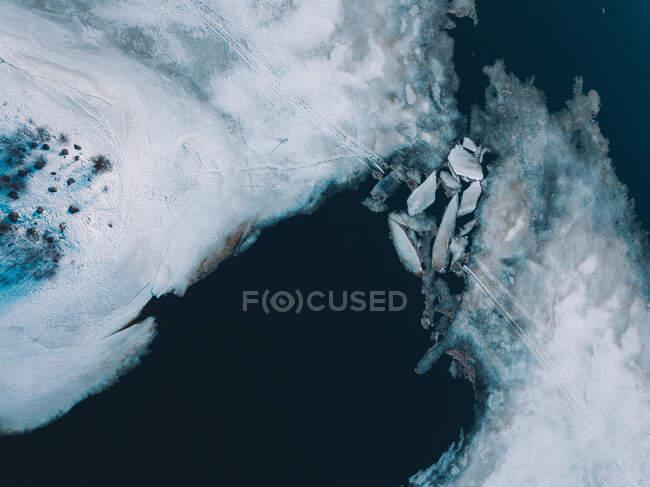 Plaques de glace brisées flottant dans les eaux froides de l'Arctique près de la côte enneigée — Photo de stock