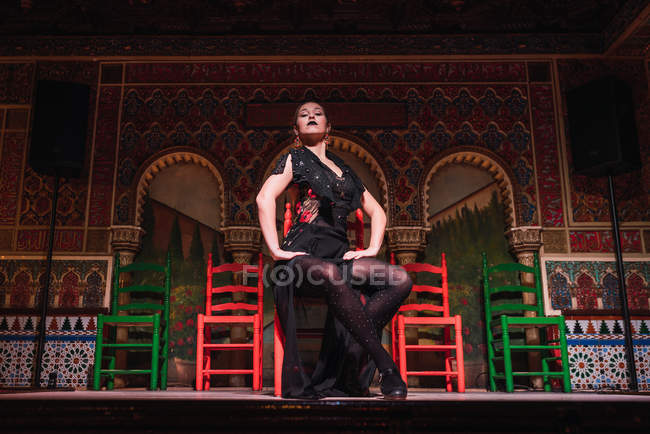 Young woman in dress dancing flamenco on scene in luxury oriental room decorated by mosaic — Stock Photo