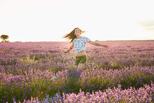 Happy attractive lady spinning between beautiful purple flowers on lavender field — Stock Photo