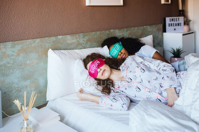 Two girls relaxed sleeping in bed with blindfold at home — Stock Photo