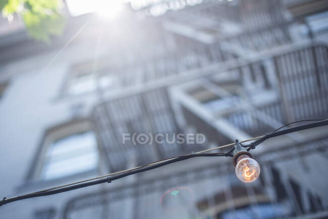 From below highlighted street lamp hanging near block of flats in sunny weather in San Francisco, USA — Stock Photo