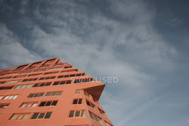 From below modern abstract red facade of block of flats and cloudy heaven in Pyrenees — Stock Photo