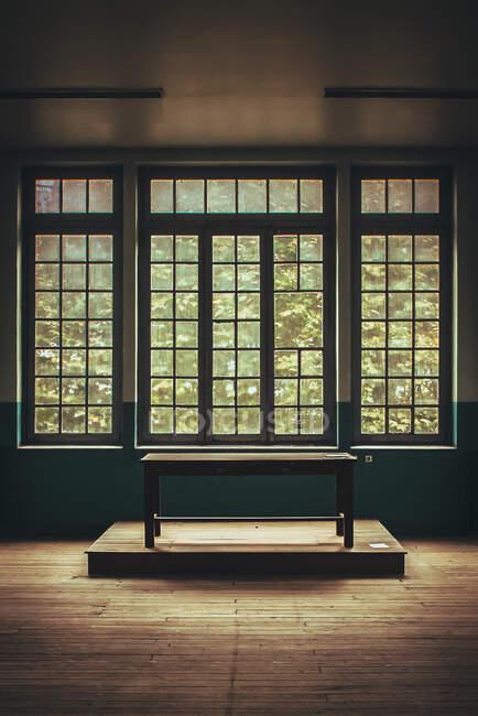 Склад дерев'яного стола біля великих вікон стоїть у порожній кімнаті. — стокове фото