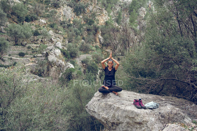 Lovely woman in sportswear keeping eyes closed and meditating while sitting in lotus pose on rough stone in beautiful park — Stock Photo